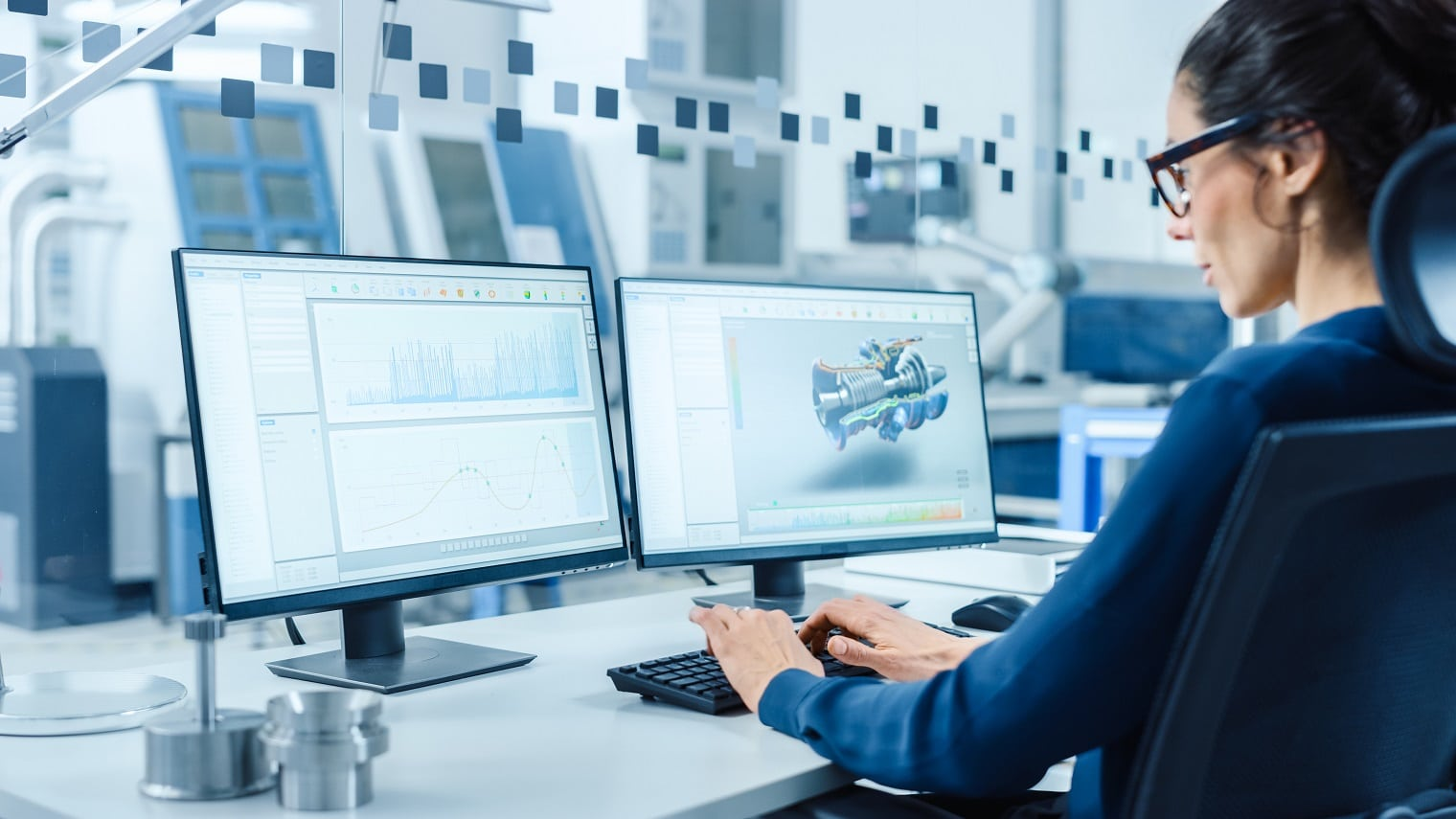 Industrial Female Engineer Working on a Personal Computer, Two Monitor Screens Show CAD Software with 3D Prototype of New Hybrid Hydrogen Engine and Charts. Modern Factory with High-Tech Machinery